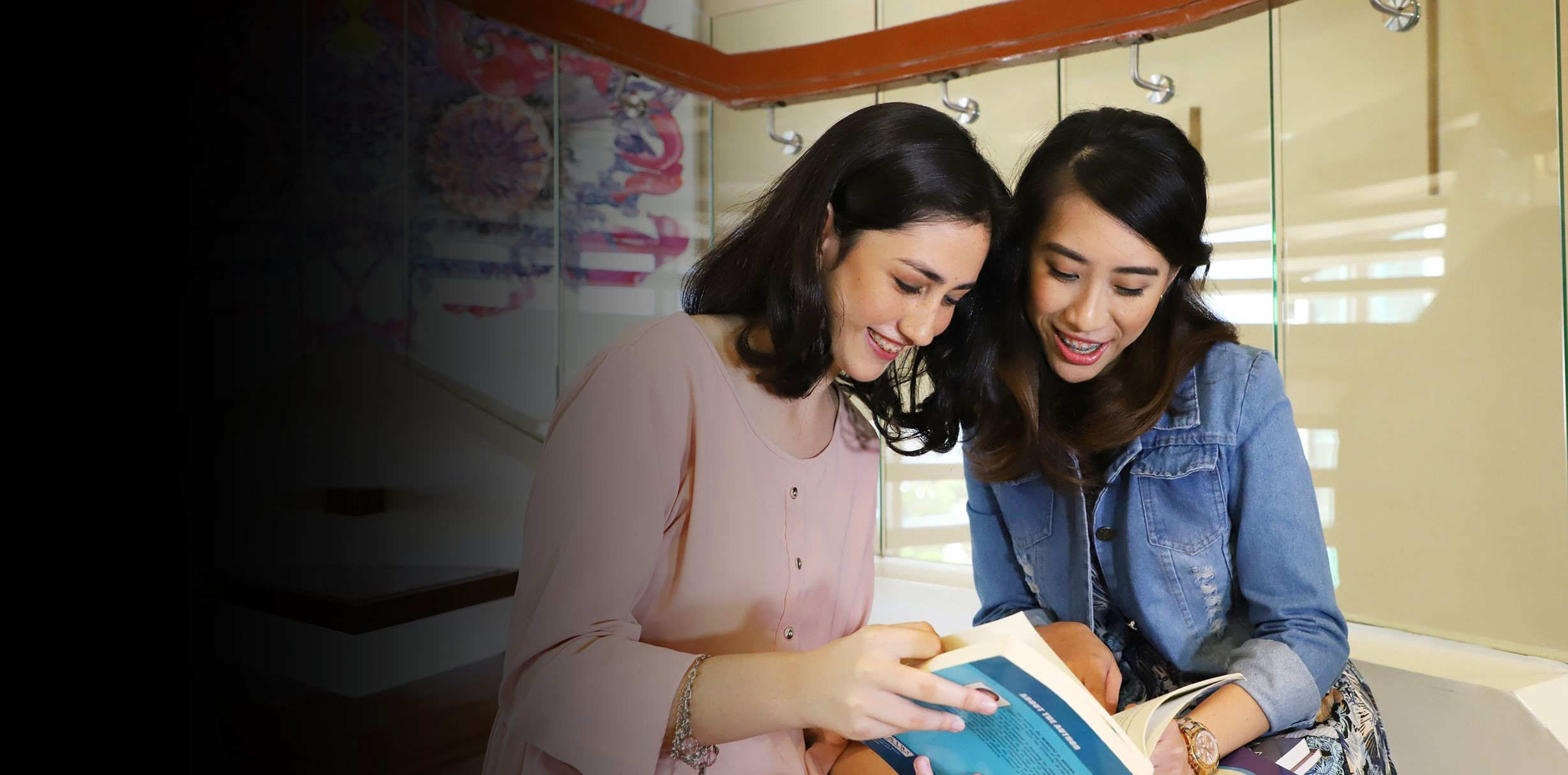 Two hospitality management college students reading a textbook